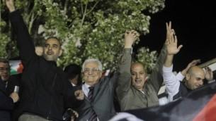 رئيس السلطة الفلسطينية محمود عباس، يحيط به السجناء الفلسطينيون الذين أطلق سراحهم مؤخرا، يحيي الحشد في رام الله، في 30 أكتوبر / تشرين الأول 2013. (Issam Rimawi/Flash90).