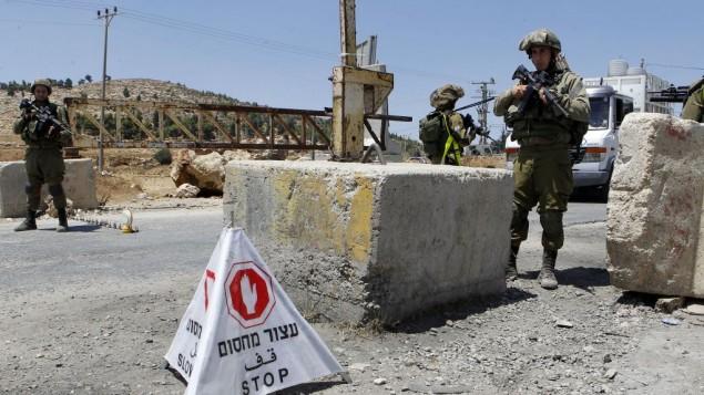 صورة توضيحية: جنود إسرائيليون يحرسون حاجزا في الضفة الغربية، 16 أغسطس، 2016. (Wisam Hashlamoun/Flash90)