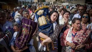 أعضاء من الحركتين اليهودتين الإصلاحية والمحافظة يحلون لفائف التوراة خلال صلاة مختلطة للنساء والرجال في الساحة العامة أمام الحائط الغربي، في البلدة القديمة في القدس، 18 مايو، 2017. (Yonatan Sindel/Flash90)