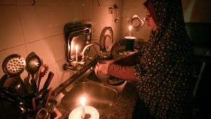 امرأة فلسطينية تغسل الصحون على ضوء الشموع في منزلها المؤقت في مخيم رفح للاجئين في جنوب قطاع غزة في 12 يونيو / حزيران 2017.  (Abed Rahim Khatib/Flash90)