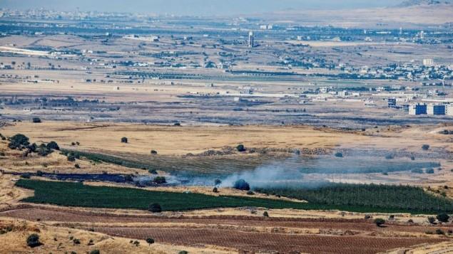 الدخان يتصاعد بالقرب من الحدود الإسرائيلية السورية، 25 يونيو 2017 (Basel Awidat/Flash90)