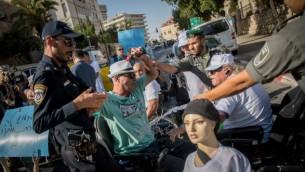 متظاهر يحاول إضرام النار في نفسه خلال تظاهرة للمطالبة بزيادة مخصصات الإعاقة أمام مقر إقامة رئيس الوزراء في القدس، 27 يونيو، 2017. (Yonatan Sindel/Flash90)