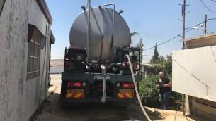مدير مستوطنة ميغداليم ياعل حشاش ينظر بينما تملأ شاحنة برج المياه في المستوطنة، 4 يونيو 2017 (Jacob Magid/Times of Israel)