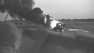 النيران مشتعلة في مركبة نقل فلسطينية جراء تعرضها لقصف من دبابة إسرائيلية خلال حرب الأيام الستة، 5 يونيو، 1967. (David Rubinger/Government Press Office)
