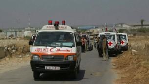 أعضاء في جمعية الصليب الأحمر يعملون على تأمين نقل مرضى فسلطينيين عند معبر إيرز في 19 يونيو، 2007. (Ahmad Khateib/ Flash90)