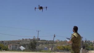 صورة شاشة من فيديو للجيش يظهر تشغيل طائرة بدون طيار محملة بكاميرا (Screen capture: IDF Spokesperson's Unit)