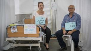 اهالي مضربون عن الطعام في الخيمة الاحتجاجية لقسم امراض الدم والسرطان للاطفال في مستشفى هداسا، في حديقة ساكر في القدس، مع شعارات عليها 'انا مضرب عن الطعام'، 25 يونيو 2017 (Yonatan Sindel/Flash90)