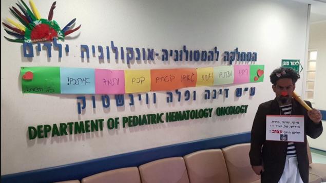 """مهرج طبي في قسم طب أمراض الأورام للأطفال في هاداسا في مارس، بعد فترة وجيزة من استقالة ستة أطباء. مكتوب على اللافتة """"المهرج  حزين اليوم،"""" (Screenshot Facebook)."""