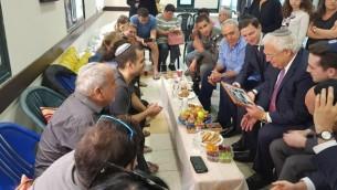 صهر الرئيس الأمريكي دونالد ترامب وكبير مساعديه، جاريد كوشنر، يوجه نظره إلى السفير الأمريكي لدى إسرائيل ديفيد فريدمان الذي يحمل صورة خلال تقديمهما التعازي لعائلة الشرطية القتيلة هداس مالكا، 21 يونيو، 2017. (Courtesy)