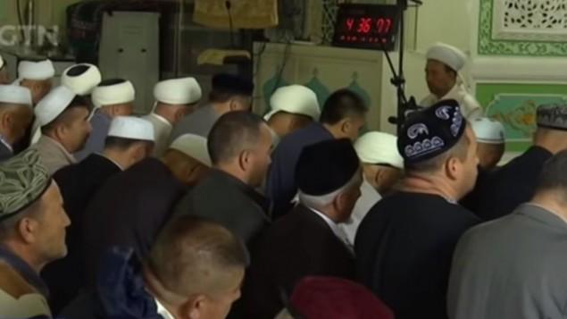 مسلمون في محافظة سنجان يصلون خلال شهر رمضان، مايو 2017 (Screen capture: YouTube)
