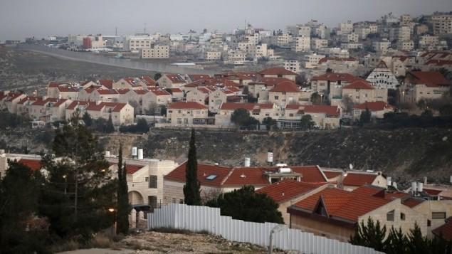 الجدار الامني الذي يفصل بين مستوطنة بسغات زئيف في القدس الشرقية من حي عناتا الفلسطيني (في الخلفية)، 15 يناير 2017 (AFP Photo/Ahmad Gharabli)