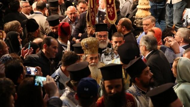 """البطريرك الأرثوذكسي اليوناني ثيوفيلوس الثالث يترأس قداس """"سبت النور"""" حيث يحتشد الآلاف في كنيسة القيامة في المدينة القديمة في القدس، 15 أبريل، 2017. (AFP PHOTO / GALI TIBBON)"""