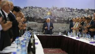 رئيس السلطة الفلسطينية محمود عباس وحكومته يقومون بتلاوة صلاة خلال جلسة في رام الله، 11 سبتمبر، 2014.(Photo credit: AFP/ ABBAS MOMANI)