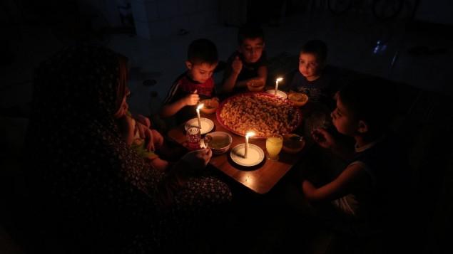 عائلة فلسطينية تتناول وجبة العشاء على ضوء الشموع في منزلهم المرتجل في مخيم رفح، جنوب قطاع غزة، خلال انقطاع للكهرباء، 11 يونيو، 2017. (AFP/SAID KHATIB)