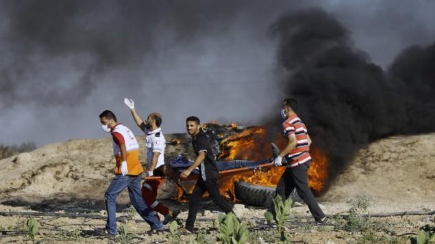 متظاهرون ومسعفون فلسطينيون يحملون مصابا خلال مواجهات مع القوات الإسرائيلية بالقرب من السياج الحدودي شرقي مخيم جباليا، في 23 يونيو، 2017. (AFP/MOHAMMED ABED)