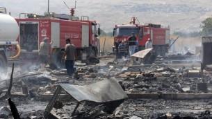 رجال اطفاء لبنانيون يفحصون الاضرار الناتجة عن حريق ضخم في مخيم لاجئين سوريين في لبنان، 2 يوليو 2017 (HASSAN JARRAH / AFP)