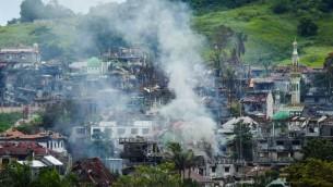 سحب الدخان تتصاعد من منازل محترقة مع استمرار المعارك بين القوات الحكومية والمسلحين الإسلاميين في مدينة مارواي الواقعة في جزيرة مينداناو جنوبي الفيليبين، 3 يوليو، 2017. (AFP PHOTO / FERDINANDH CABRERA)