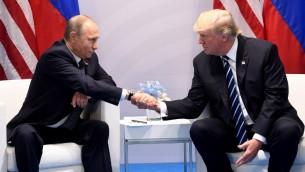 الرئيس الأمريكي دونالد ترامب ونظيره الروسي فلاديمير بوتين يتصافحان خلال لقاء جمعهما على هامش قمة العشرين في هامبورغ، ألمانيا، 7 يوليو، 2017. (AFP PHOTO / SAUL LOEB)