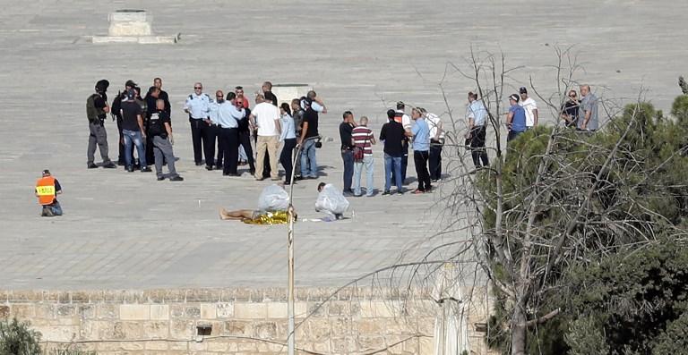 الشرطة الإسرائيلية تقوم بتمشيط المكان وتحيط بجثة في الموقع الذي قام فيه ثلاثة مسلحين عرب مواطني إسرائيل بقتل شرطيين إسرائيليين في الحرم القدسي، 14 يوليو، 2017.  (AFP PHOTO / THOMAS COEX)