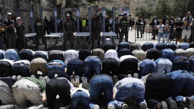 مصلون مسلمون يصلون خارج الحرم القدسي احتجاجا على وضع بوابات إلكترونية عند مدخل الموقع المقدس في أعقاب الهجوم الذي وقع قبل يومين، 16يوليو، 2017 (AFP PHOTO / Menahem KAHANA)
