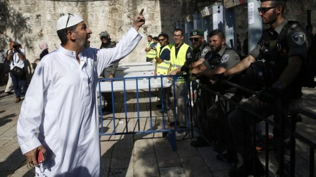 رجل فلسطيني امام حرس حدود اسرائيليين بالقرب من بوابات كشف المعادن عند المدخل الرئيسي للحرم القدسي، 16 يوليو 2017 (AFP PHOTO / AHMAD GHARABLI)