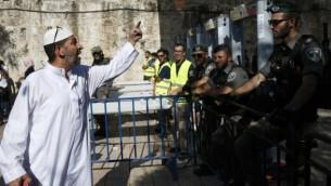 رجل فلسطيني يجادل أفراد من شرطة حرس الحدود بالقرب من البوابات الإلكترونية التي تم وضعها حديثا عن المدخل الرئيسي للمسجد الأقصى في البلدة القديمة في القدس، 16 يوليو، 2017، بعد إعادة فتح الموقع الحساس. (AFP PHOTO / AHMAD GHARABLI)