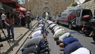 مصلون مسلمون يرفضون الدخول إلى الحرم القدسي بسبب الإجراءات الأمنية الجديدة التي فرضتها السلطات الإسرائيليون يقومون بالصلاة خارج باب الأسباط في البلدة القديمة في مدينة القدس، 17 يوليو، 2017. (AFP/AHMAD GHARABLI)