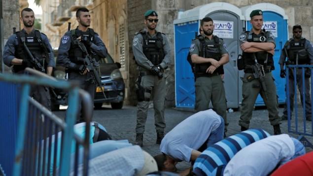 قوات الأمن الإسرائيلية تقف أمام المصلين المسلمين الفلسطينيين الذين يصلون خارج بوابة الأسباط، المدخل الرئيسي لمجمع الحرم القدسي في البلدة القديمة في القدس، في 19 يوليو / تموز 2017. (AFP PHOTO / Ahmad GHARABLI)