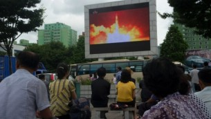 أشخاص يشاهدون تغطية اختبار صاروخ بالستي عابر للقارات على شاشة في ساحة عامة في بيونغ يانغ، 29  يوليو، 2017. (AFP PHOTO / Kim Won-Jin)