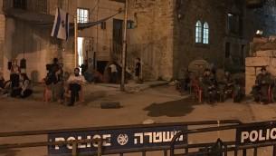 المستوطنون في منزل استولى عليه مستوطنين في الخليل يجلسون خارج المبنى بجوار عناصر حرس الحدود، 26 يوليو 2017 (Jacob Magid)