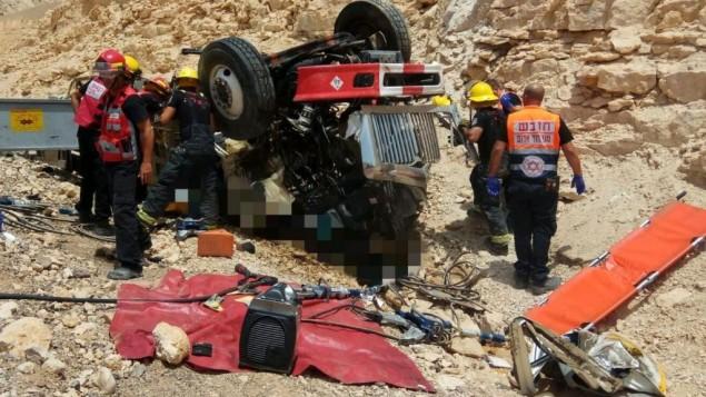 مسعفون ورجال إطفاء يقوموم بسحب رجلين من شاحنة انقلبت على طريق سريع شمال مدينة إيلات، 13 يونيو، 2017. (نجمة داوود الحمراء)