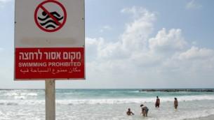 إشارة تحذر السابحين من الظروف الخطيرة على شاطئ غير ذي  رقابة  في تل أبيب. (Gili Yaari/Flash90)