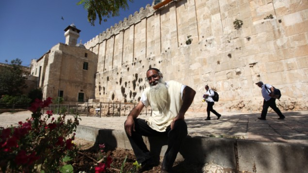 مستوطن يهودي يجلس خارج الحرم الإبراهيمي في مدينة الخليل في الضفة الغربية. (Kobi Gideon/Flash90)