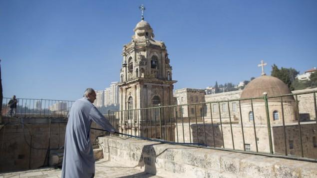"""راهب أرثوذكسي في """"دير الصليب"""" يحمل خرطوم مياه وهو يقف على  سقف الدير أثناء اندلاع حريق في 'وداي الصليب'، وسط القدس، 2 يوليو، 2013. (FLASH90)"""