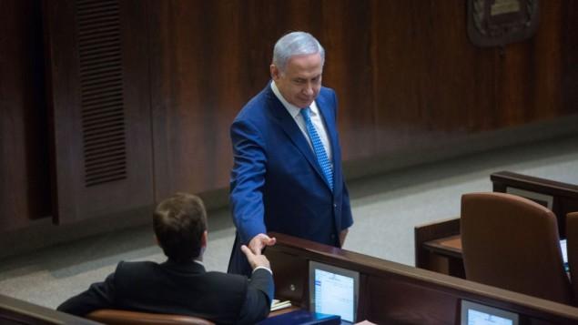 رئيس الوزراء بنيامين نتنياهو، يقف ويتصافح مع زعيم حزب الاتحاد الصهيوني المعارض يتسحاق هرتسوغ خلال جلسة عامة خاصة بمناسبة الذكرى الخمسين للكنيست، 19 يناير / كانون الثاني 2016.  (Yonatan Sindel/Flash90)