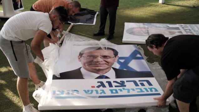 عمال يحملون ملصقات انتخابية كبيرة خلال تجمع لداعمي رئيس حزب العمل يتسحاك هرتسوغ في تل ابيب، 26 يونيو 2017 (Tomer Neuberg/Flash90)