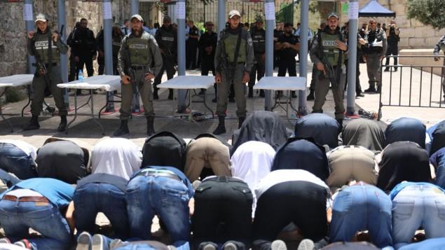 مصلون مسلمون يصلون خارج الحرم القدسي احتجاجا على وضع بوابات إلكترونية عند مدخل الموقع المقدس في أعقاب الهجوم الذي وقع قبل يومين، 16يوليو، 2017. (Yonatan Sindel/Flash90)