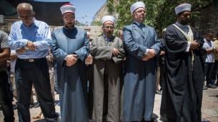 مسؤولون في الأوقاف الإسلامية وأخرون يستعدون للصلاة خارج الحرم القدسي، في البلدة القديمة في مدينة القدس، ويرفضون الدخول إلى المجمع عبر البوابات الإلكترونية التي وضعتها إسرائيل بعد هجوم وقع في المكان، 16 يوليو، 2017. (Yonatan Sindel/Flash90)