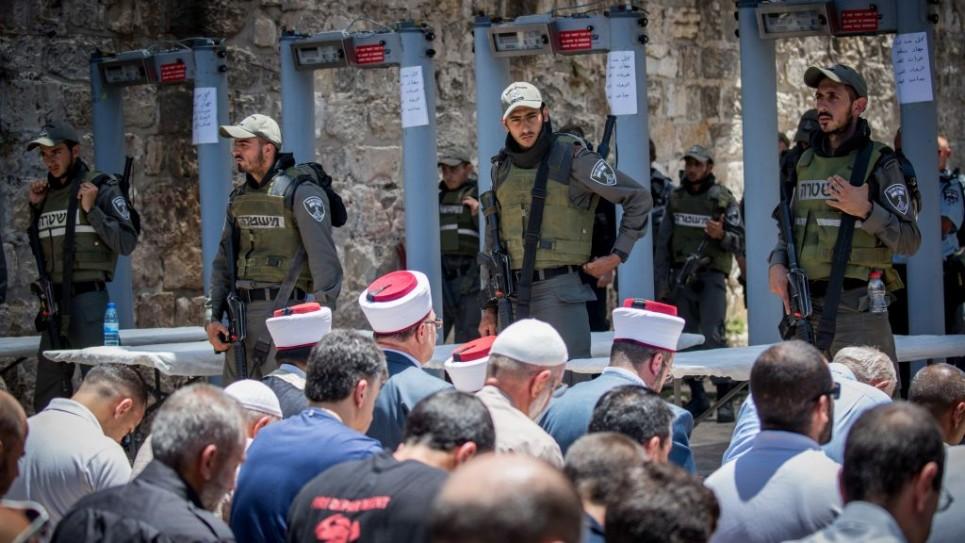 مسؤولو الوقف يقودون صلاة المسلمين خارج المسجد الأقصة في البلدة القديمة في القدس في 16 يوليو / تموز. قال مسؤولو الأوقاف  للمصلين المسلمين أن لا يدخلون المسجد عن طريق كاشفات معدنية مثبتة من قبل إسرائيل لأغراض أمنية بعد الهجوم في 14 يوليو / تموز والذي فيه ثلاثة عرب إسرائيليين ظهروا في ساحة المسجد وقتلوا اثنين من ضباط حرس الحدود الإسرائيليين. (Yonatan Sindel/Flash90)