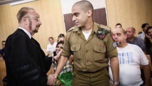 إيلور عزاريا يصافح محاميه يورام شيفطل قبل بدء جلسة المحكم في مقر الجيش الإسرائيلي في تل أبيب، 17 يوليو، 2017. (Miriam Alster/Flash90)