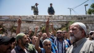 مصلين مسلمين يرددون هتافات في باب الأسباط، خارج الحرم القدسي الشريف، في مدينة القدس القديمة، في 19 يوليو 2017. (Yonatan Sindel/Flash90)