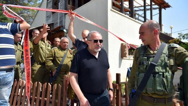 وزير الدفاع أفيغدور ليبرمان، وسط الصور، في موقع الهجوم الذي وقع في مستوطنة حلميش حيث قُتل ثلاثة إسرائيليين وجُرحت أخرى في هجوم طعن نفذع فلسطيني، 22 يوليو، 2017.  (Hermoni/Ministry of Defense)
