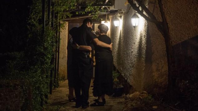 رجل شرطة يحتضن سيدة تعيش بالقرب من المنزل الذي قُتل فيه ثلاثة إسرائيليون في هجوم طعن وقع في اليوم السابق في مستوطنة حلميش الواقعة في الضفة الغربية، السبت، 22 يوليو، 2017. (Hadas Parush/FLASH90)