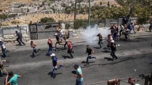 متظاهرون فلسطينيون يهربون من قنابل الغاز المسيل للدوع بعد صلاة الجمعة في حي وادي الجوز في القدس الشرقية، 28 يوليو 2017 (Miriam Alster/Flash90)