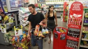 إسرائيليون يتسوقون في متجر صغير في تل أبيب، 4 يوليو 2014. (Flash90)