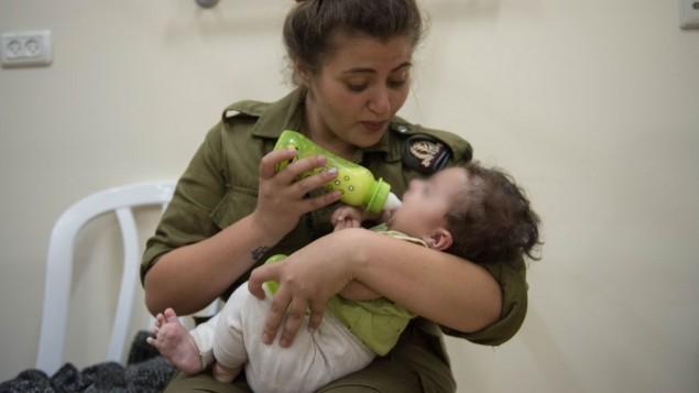 في هذه الصورة غير المؤرخة المقدمة في 19 يوليو، 2017 تقوم جندية إسرائيلية بإطعام  طفل سوري في إطار برنامج  الجيش 'حسن الجوار'  لتقديم المساعدة الإنسانية  للمدنيين السوريين على الجانب السوري من هضبة الجولان (IDF spokesperson)