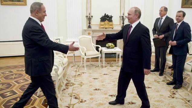 رئيس الوزراء بينيامين نتنياهو والرئيس الروسي فلاديمير بوتين (من اليسار) يتصافحان خلال لقاء جمعهما في موسكو، 9 مارس، 2017.(AFP Photo/Pool/Pavel Golovkin)