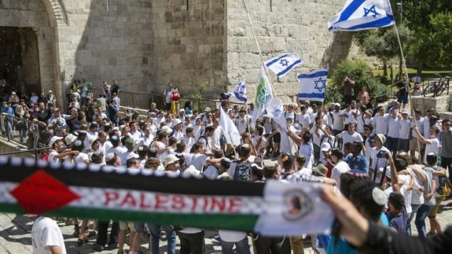 نساء فلسطينيات يحلمن وشاحا يحمل اسم فلسطين، بينما يحمل شبيبة إسرائيليون الأعلام الإسرائيلية خلال 'مسيرة العلم' التي تمر عبر باب العامود في البلدة القديمة في مدينة القدس خلال الاحتفالات الإسرائيلية ب'يوم القدس'، 17 مايو، 2015. (AFP Photo/Jack Guez)