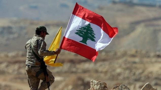 يحمل أحد عناصر حزب الله اللبناني وأعلام حزب الله ولبنان خلال جولة صحفية بالقرب من بلدة عرسال الحدودية في 25 يوليو / تموز 2017.  (AFP Photo/Stringer)