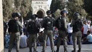 قوى الأمن الإسرائيلية تقف أمام المصلين الفلسطينين في الحرم القدسي في 27 يوليو، 2017، مع المسجد الأقصى في الخلفية. (AFP PHOTO / AHMAD GHARABLI)
